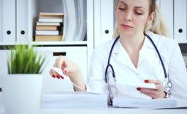 Γραφειοκρατία στο νοσοκομείο Νέα θηλυκή εργασία γιατρών με τους σωρούς των αρχείων στοκ εικόνες