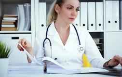 Γραφειοκρατία στο νοσοκομείο Νέα θηλυκή εργασία γιατρών με τους σωρούς των αρχείων στοκ εικόνα με δικαίωμα ελεύθερης χρήσης