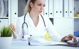 Γραφειοκρατία στο νοσοκομείο Νέα θηλυκή εργασία γιατρών με τους σωρούς των αρχείων στοκ εικόνες με δικαίωμα ελεύθερης χρήσης