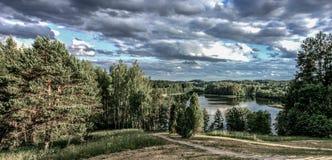 Γραφική άποψη σχετικά με τη λίμνη και το δάσος στο χρόνο βραδιού αμέσως πριν από το ηλιοβασίλεμα Ουρανός και σύννεφα που απεικονί Στοκ Φωτογραφία