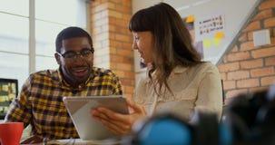 Γραφικοί σχεδιαστές που συζητούν πέρα από ψηφιακό στο γραφείο σε ένα σύγχρονο γραφείο 4k φιλμ μικρού μήκους