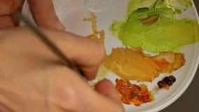 Γραφικός καλλιτέχνης που αναμιγνύει τα χρώματα ελαιοχρώματος στην παλέτα απόθεμα βίντεο