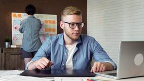 Γραφικός σχεδιαστής που σύρει το νέο σχέδιο που χρησιμοποιεί την ταμπλέτα γραφικής παράστασής του απόθεμα βίντεο