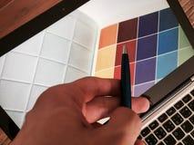 Γραφικός σχεδιαστής στην εργασία χαρακτηριστικά χρώματος εικόνας δείγματα εκτύπωσης Τύπου βιομηχανίας προ στοκ φωτογραφία