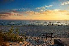 Γραφικό ηλιοβασίλεμα σε μια αμμώδη παραλία Στοκ Εικόνες