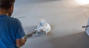 Γυαλίζοντας άμμος Laborer και πάτωμα κατεβατών τσιμέντου στοκ φωτογραφία
