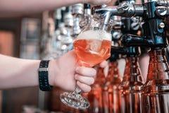 Γυαλί εκμετάλλευσης μπάρμαν γεμίζοντας το με τη σκοτεινή μπύρα τεχνών στοκ εικόνες