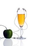 Γυαλί και μήλο με τα ακουστικά Στοκ Φωτογραφίες