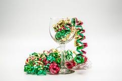 Γυαλί κρασιού που περιβάλλεται από την κατσαρώνοντας κορδέλλα Χριστουγέννων Στοκ Φωτογραφία