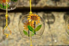 Γυαλί με τους κίτρινους ηλίανθους που κρεμούν από το κίτρινο σχοινί σε ξύλινο στοκ φωτογραφία