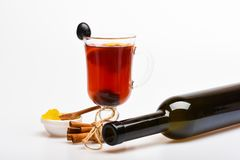 Γυαλί με το θερμαμένο κρασί με το σταφύλι και την κανέλα και το μπουκάλι του κρασιού Εποχιακή έννοια ποτών Γυαλί με το θερμαμένο  Στοκ φωτογραφία με δικαίωμα ελεύθερης χρήσης