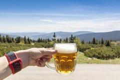 Γυαλί μπύρας εκμετάλλευσης ατόμων στο βουνό, Krkonose, τσεχικά βουνά στοκ εικόνες