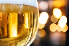 Γυαλί μπύρας με τον αφρό, τη νύχτα με τα θερμά φω'τα και bokeh στοκ φωτογραφία
