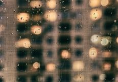 Γυαλί που καλύπτεται με τη βροχή, μέσω της οποίας μπορείτε να δείτε τα παράθυρα ο στοκ φωτογραφία
