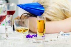 Γυαλί του οινοπνεύματος με τη μεθυσμένη γυναίκα ύπνου πίσω Στοκ εικόνες με δικαίωμα ελεύθερης χρήσης