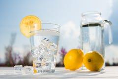 Γυαλί του πάγου και του νερού που διακοσμούνται με μια φέτα του λεμονιού που στέκεται σε έναν άσπρο πίνακα ενάντια σε μια καράφα  Στοκ Εικόνα