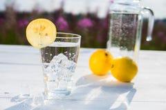 Γυαλί του πάγου και του νερού που διακοσμούνται με μια φέτα του λεμονιού που στέκεται σε έναν άσπρο πίνακα ενάντια σε μια καράφα  Στοκ Εικόνες