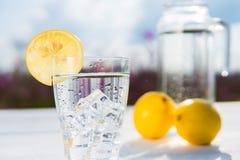 Γυαλί του πάγου και του νερού που διακοσμούνται με μια φέτα του λεμονιού που στέκεται σε έναν άσπρο πίνακα ενάντια σε μια καράφα  Στοκ φωτογραφίες με δικαίωμα ελεύθερης χρήσης
