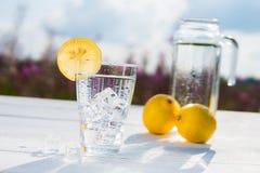 Γυαλί του πάγου και του νερού που διακοσμούνται με μια φέτα του λεμονιού που στέκεται σε έναν άσπρο πίνακα ενάντια σε μια καράφα  Στοκ Φωτογραφίες
