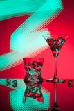 Γυαλιά ένας Martini κοκτέιλ πάγος ουίσκυ, στο κόκκινο κλίμα των όμορφων ελαφριών αποτελεσμάτων Στοκ Φωτογραφίες