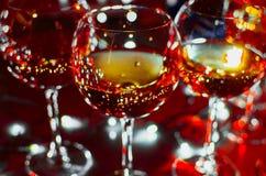 Γυαλιά γυαλιού με το κρασί στο υπόβαθρο των φωτεινών γιρλαντών Στοκ Εικόνες