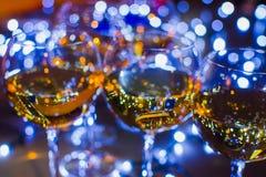 Γυαλιά γυαλιού με το κρασί στο υπόβαθρο των φωτεινών γιρλαντών Στοκ εικόνα με δικαίωμα ελεύθερης χρήσης