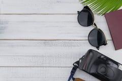 Γυαλιά ηλίου, κάμερα ταινιών και διαβατήριο με τα φύλλα φτερών Στοκ Εικόνες