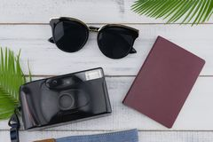 Γυαλιά ηλίου, κάμερα ταινιών και διαβατήριο με τα φύλλα φτερών Στοκ εικόνα με δικαίωμα ελεύθερης χρήσης
