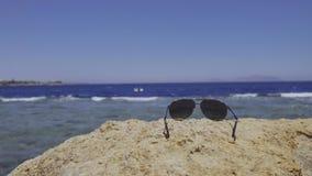 Γυαλιά ηλίου που βρίσκονται στην πέτρα απόθεμα βίντεο