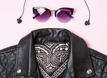 Γυαλιά ηλίου σακακιών και γυναικών ποδηλατών με τα ακουστικά στο ρόδινο υπόβαθρο Εναλλακτικό σύνολο μόδας Επίπεδος βάλτε, τοπ άπο Στοκ Εικόνες