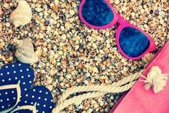 Γυαλιά ηλίου, σανδάλια πτώσης κτυπήματος και τσάντα παραλιών στην παραλία Στοκ Εικόνες