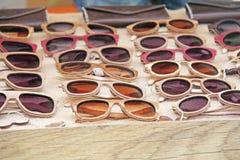 Γυαλιά ηλίου σε ένα ξύλινο πλαίσιο πολλά γυαλιά ηλίου Γυαλιά σχεδιαστών Στοκ Εικόνα