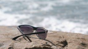 Γυαλιά ηλίου στην πέτρα θαλασσίως απόθεμα βίντεο