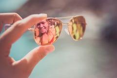 Γυαλιά ηλίου στο θηλυκό χέρι στην παραλία με την αντανάκλαση στοκ εικόνες