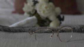 Γυαλιά και ανθοδέσμη του μακρο πυροβολισμού ολισθαινόντων ρυθμιστών νυφών απόθεμα βίντεο