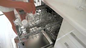 Γυαλιά και γυαλικά φόρτωσης γυναικών στη μηχανή πλυντηρίων πιάτων φιλμ μικρού μήκους