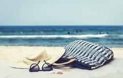 Γυαλιά καπέλων αχύρου, τσαντών και ήλιων σε μια τροπική παραλία στοκ εικόνα με δικαίωμα ελεύθερης χρήσης