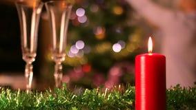 Γυαλιά κεριών και σαμπάνιας Χριστουγέννων με τη διακόσμηση χριστουγεννιάτικων δέντρων στο υπόβαθρο απόθεμα βίντεο