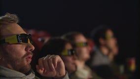 Γυαλιά κινηματογράφων απογείωσης ατόμων στον κινηματογράφο σε σε αργή κίνηση Κουρασμένος από τον τρισδιάστατο κινηματογράφο φιλμ μικρού μήκους