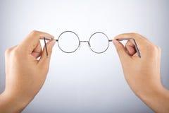 Γυαλιά κύκλων εκμετάλλευσης χεριών Στοκ Φωτογραφία