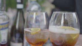 Γυαλιά λαμπιρίζοντας κρασιού τα φρέσκους κοκτέιλ, τα εσπεριδοειδή και τον πάγο που γεμίζουν με με το λαμπιρίζοντας νερό Πλαίσιο Θ φιλμ μικρού μήκους