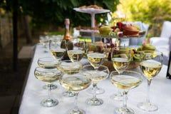 Γυαλιά με τη σαμπάνια και το άσπρο κρασί ενώπιον του κόμματος στον καφέ Στοκ Εικόνες