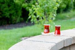 Γυαλιά με το καυτό τουρκικό τσάι στον τοίχο στηθαίων τούβλου Στοκ Εικόνες