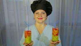 Γυαλιά με το κοκτέιλ νωπών καρπών στα χέρια μιας χαμογελώντας γυναίκας μαγείρων φιλμ μικρού μήκους