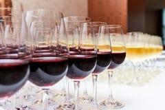 Γυαλιά με το κόκκινο και άσπρο κρασί σε έναν άσπρο πίνακα Στοκ Φωτογραφίες