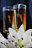 Γυαλιά με το λουλούδι κρασιού και κρίνων στο μαύρο μετάξι Στοκ φωτογραφία με δικαίωμα ελεύθερης χρήσης