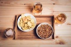Γυαλιά μπύρας και πρόχειρα φαγητά μπύρας στον ξύλινο πίνακα κόκκινος τρύγος ύφους κρίνων απεικόνισης Στοκ Φωτογραφία
