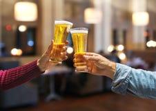 Γυαλιά μπύρας που αυξάνονται στα χέρια φρυγανιάς κινηματογραφήσεων σε πρώτο πλάνο με τα γυαλιά Στοκ Φωτογραφίες