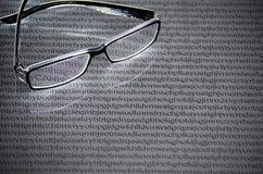 Γυαλιά σε ένα άσπρο υπόβαθρο των τυχαίων επιστολών του αγγλικού αλφάβητου στοκ εικόνες