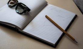 Γυαλιά σημειωματάριων και ένα μολύβι στον πίνακα στοκ φωτογραφία με δικαίωμα ελεύθερης χρήσης
